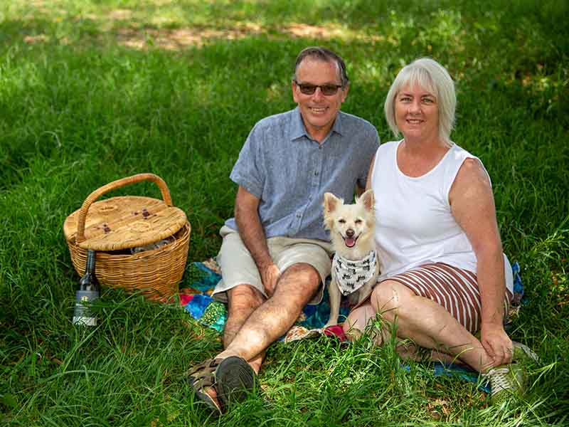 Lady and man sitting on picnic rug on grass with dog, picnic basket and bottle of wine..