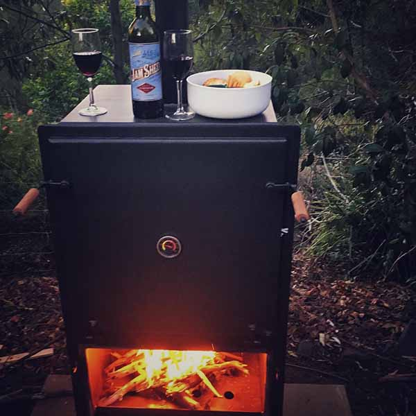 Wood fired pizza oven with bottle of red wine, wine glasses and bowl of snacks.